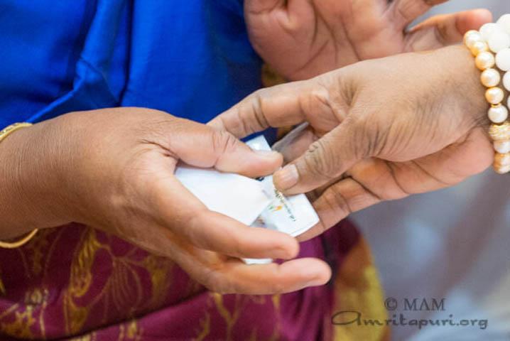 Amma donnant des paquets de graines en même temps que le prasad